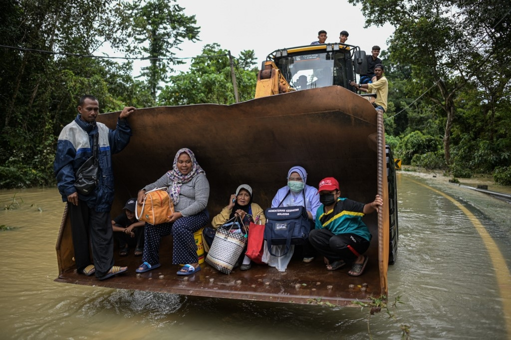 malaysian villagers escape floods on excavator as 28000 evacuated