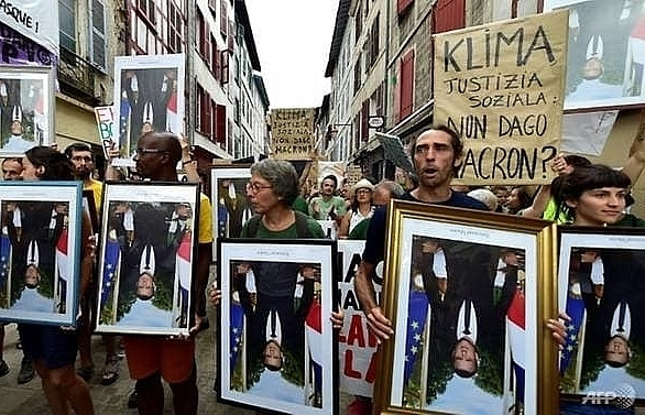 anti g7 activists march with stolen macron portraits