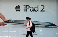 A woman checks her mobile phone while walking past advertising for the ipad 2 in Beijing. A debt-laden Chinese computer firm embroiled in a copyright row with Apple over the iPad name on Friday threatened to sue the technology giant in the United States for $2 billion