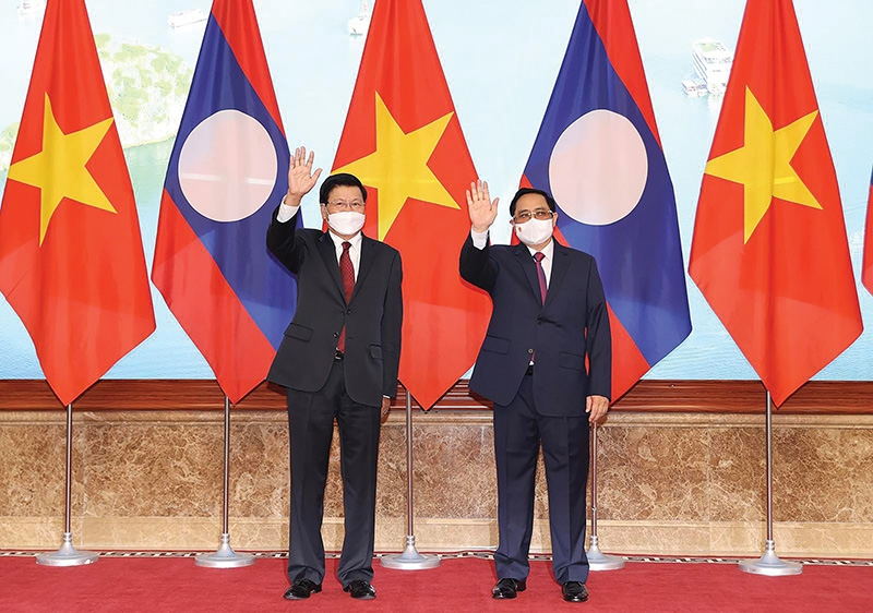 Vietnamese Prime Minister Pham Minh Chinh (right) receives Thongloun Sisoulith, State President and General Secretary of the Lao People's Revolutionary Party