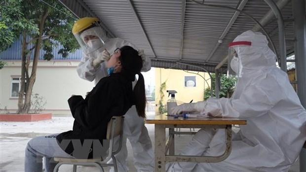 Medical workers collect samples for COVID-19 testing. (Photo: VNA)