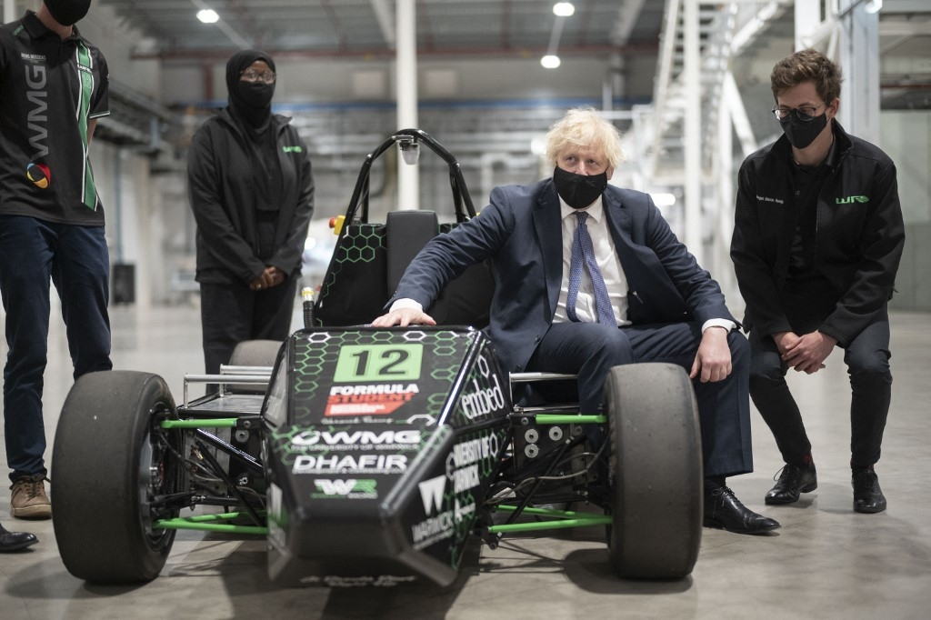 Britain's Prime Minister Boris Johnson (C), chats to Warwick University engineering students as he looks at their electric racing car which they are developing with sponsorship from the facility, during a visit to the UK Battery Industrialisation Centre in Coventry, central England on July 15, 2021. David Rose / POOL / AFP