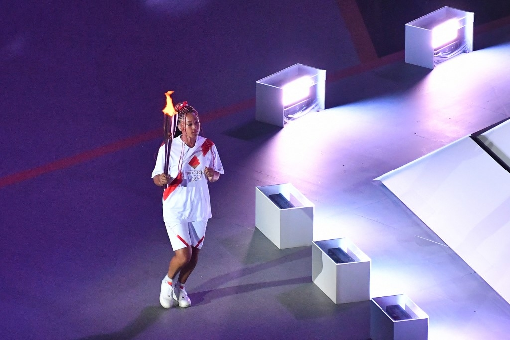 An overview shows Japan's tennis player Naomi Osaka carrying the Olympic torch in the Olympic Stadium during the opening ceremony of the Tokyo 2020 Olympic Games, in Tokyo, on July 23, 2021. Antonin THUILLIER / AFP