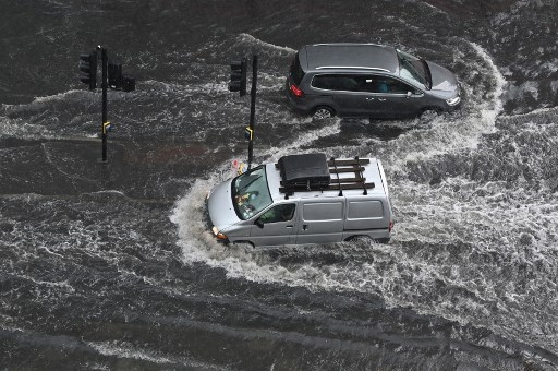 Vehicles drive through deep water on a flooded road in The Nine Elms district of London on July 25, 2021 during heavy rain. Buses and cars were left stranded when roads across London flooded on Sunday, as repeated thunderstorms battered the British capital. JUSTIN TALLIS / AFP