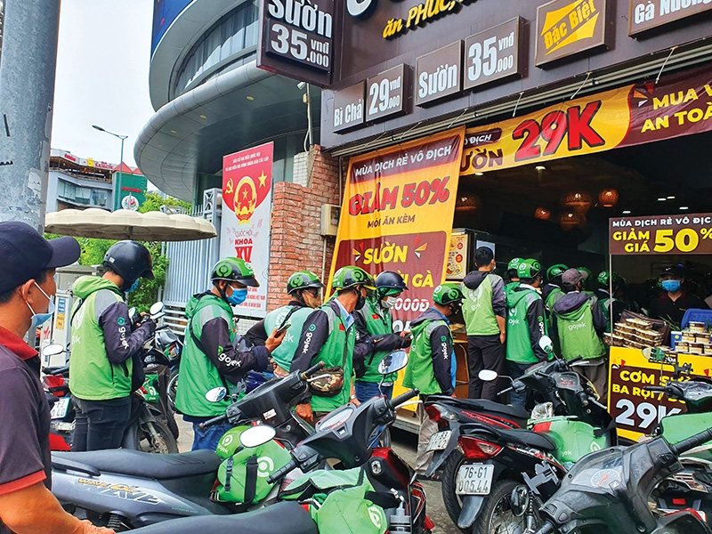 Virus-hit areas are trying to smooth out measures on delivery services, Photo: Le Toan