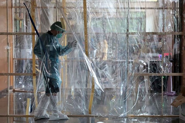 A medic walks through a building that is being transformed into an isolation centre for COVID-19 patients in Bangkok (Photo: Bangkok Post)