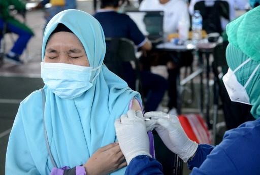 A woman receives the Sinovac Covid-19 coronavirus vaccine during a mass vaccination at Praja Raksaka Udayana Military Regional Command in Denpasar, on Indonesia's resort island of Bali on August 4, 2021. SONNY TUMBELAKA / AFP