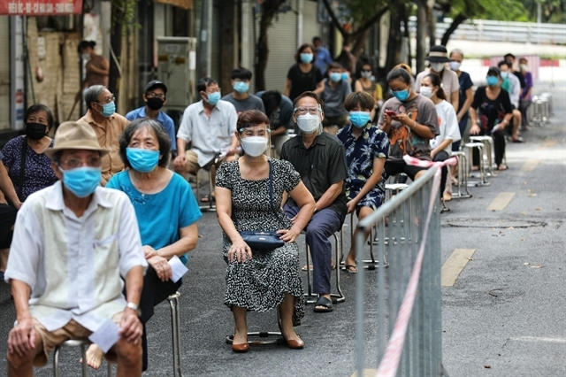 People living in Le Dai Hanh ward in Hanoi's Hai Ba Trung district, wait to be tested for  COVID-19.- VNA/VNS Photo